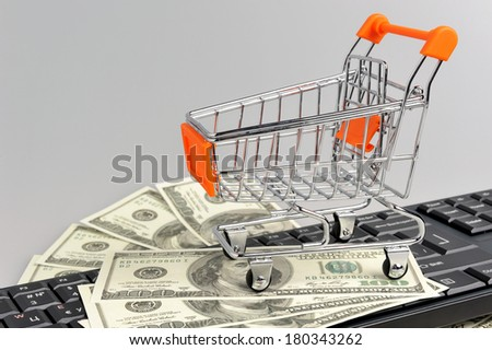 Shopping cart with money on black keyboard on gray background - stock photo
