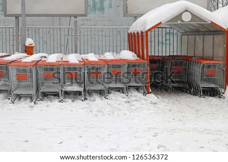 Shopping carts under the snow at supermarket parking lot