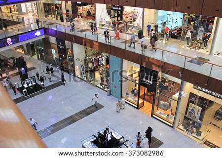 shopping center Dubai Mall, top view inside, boutiques and people make purchases, United Arab Emirates April 14, 2014, soft focus - stock photo