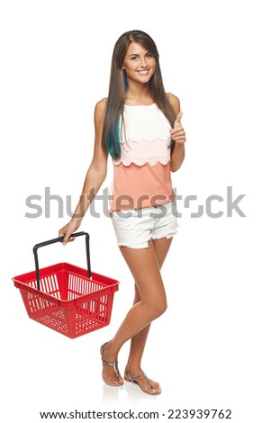 Shopping concept. Happy full length woman walking with empty red shopping basket and gesturing thumb up, white background - stock photo