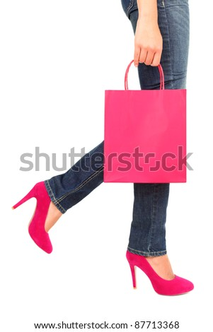 Shopping concept. Shopping bag, jeans, and high heels closeup with copy space on shopping bag. Shopping woman profile close up isolated on white background, Pink / red bag and shoes. - stock photo