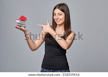 Shopping concept. Smiling young woman holding small  supermarket shopping cart on her palm with the credit card  on grey background. - stock photo