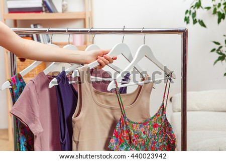 Shopping concept. Woman choosing dresses during shopping or being in wardroom at home. - stock photo