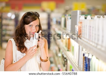 Shopping cosmetics - woman smelling bottle of shampoo in drug-store - stock photo