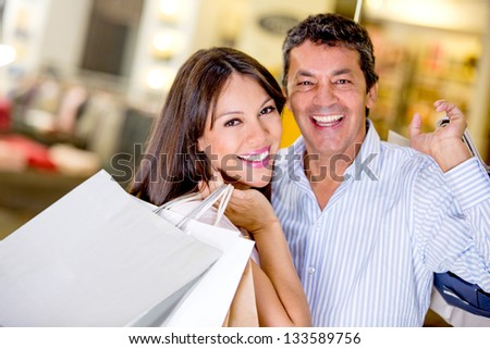 Shopping couple smiling and looking very happy - stock photo