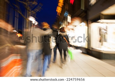 Shopping crowd walking on sidewalk at dusk