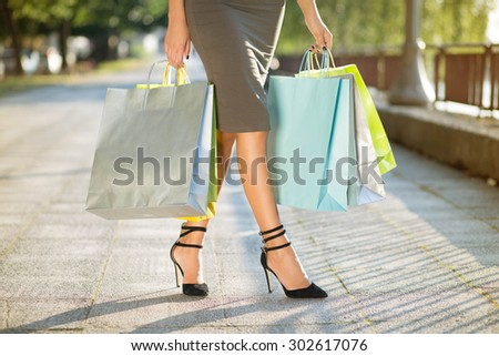 Shopping day. Unrecognizable female person carrying lots of colorful shopping bags.  - stock photo