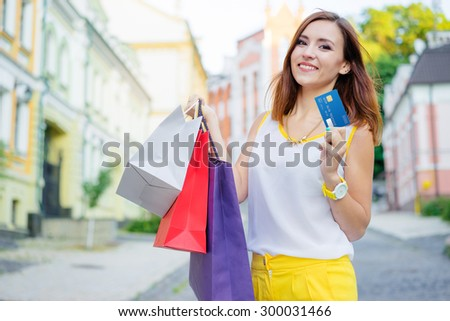 Shopping day with credit card. Attractive young woman with paper bags walking on city street. - stock photo