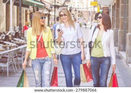 Shopping Female Friends with bags on the street.Group of caucasian women purchasing in the city.