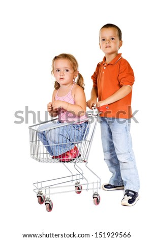 Shopping for a little sister - boy pushing shopping cart with a girl inside - stock photo