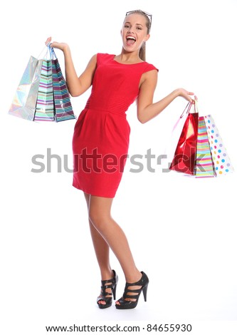 Shopping gift bags held by beautiful sexy young woman with lovely happy smile, wearing black high heeled shoes and short red dress. She has blond brown hair and sunglasses. - stock photo