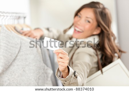 Shopping gift card sign. Woman shopper showing empty blank sign in clothing store. Beautiful excited smiling asian caucasian female model. - stock photo