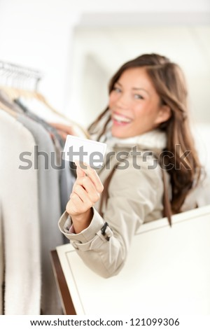 Shopping gift card woman happy showing business card or blank paper sign in clothes shop. Beautiful smiling mixed race Asian Caucasian young model. - stock photo