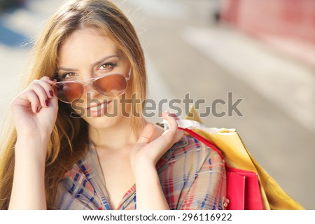 Shopping Girl in front of shopping center holding shopping bags - stock photo