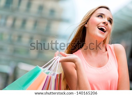 Shopping girl looking up daydreaming and holding bags - stock photo