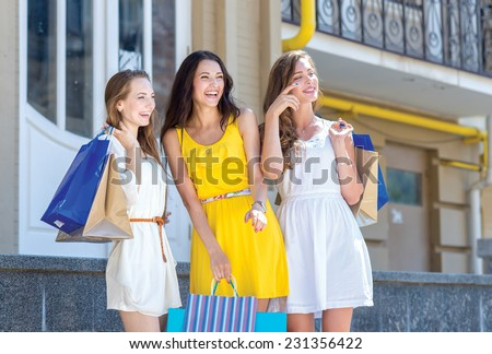 Shopping in a good mood. Three young and pretty girls are standing with shopping bags in a great mood. They are smiling and having fun - stock photo