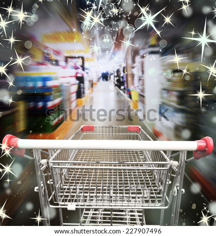 Shopping in supermarket. Shoping cart with christmas lights - stock photo
