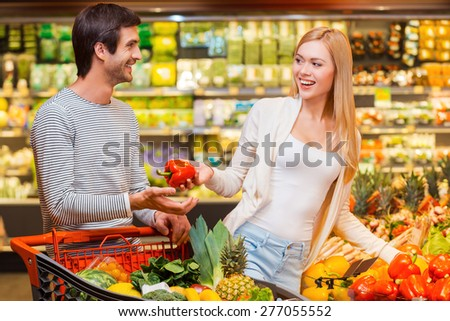 Shopping is a fun. Happy young women giving red pepper to her boyfriend while shopping in a food store - stock photo