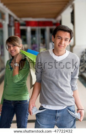 Shopping man with empty pockets and his girlfriend behind