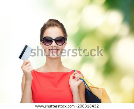 shopping, sale, christmas and holiday concept - smiling elegant woman in red dress with shopping bags and plastic card - stock photo
