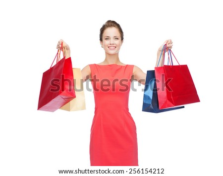 shopping, sale, christmas and holiday concept - smiling elegant woman in red dress with shopping bags - stock photo
