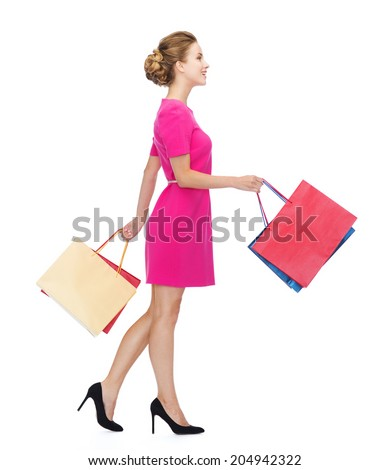 shopping, sale, gifts and holidays concept - smiling woman in pink dress with shopping bags