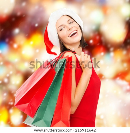 shopping, sale, gifts, christmas concept - smiling woman in red dress and santa helper hat with shopping bags - stock photo