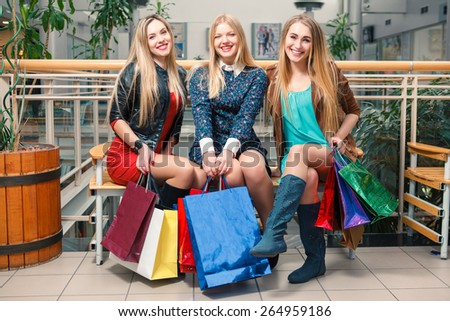 shopping, sale, happy people and tourism concept - three beautiful girls with shopping bags sitting in the mall
