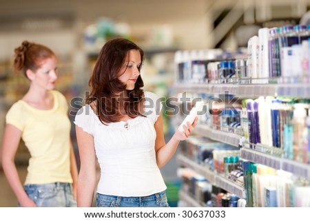 Shopping series - Woman holding bottle of shampoo in cosmetics department