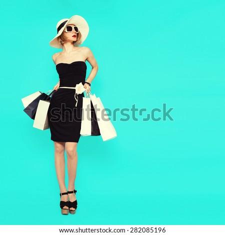 Shopping Style. Glamorous Lady holding bags on blue background - stock photo