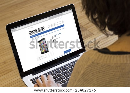 shopping, technology and internet concept: close up view of a young girl shopping with laptop computer on a fictional shop - stock photo