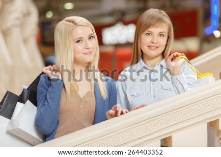 Shopping therapy. Close-up of two beautiful blond women standing on the stairs of the shopping center and holding shopping bags - stock photo