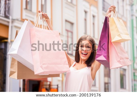 Shopping therapy makes her happy. Attractive young woman holding shopping bags and smiling while standing outdoors - stock photo