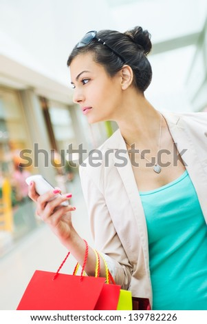 Shopping time, woman at shopping mall, looking at windows, holding cell phone