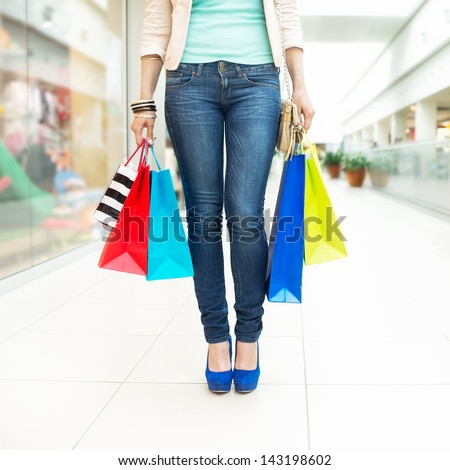 Shopping time Young woman with shopping bags at mall, with copy space - stock photo