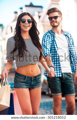 Shopping together. Cheerful young loving couple holding hands and smiling while walking along the street  - stock photo