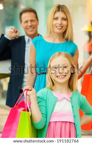 Shopping together is fun. Cheerful family holding shopping bags and smiling at camera while standing in shopping mall - stock photo