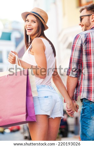 Shopping together is fun! Rear view of beautiful young loving couple walking by the street while beautiful woman carrying shopping bags and looking over shoulder  - stock photo