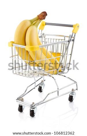 Shopping trolley full of bananas on white background - stock photo