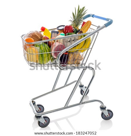 Shopping trolley full of fresh groceries isolated on a white background. - stock photo