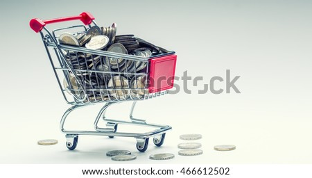 Shopping trolley. Shopping cart. Shopping trolley full of euro money - coins - currency. Symbolic example of spending money in shops, or advantageous purchase in the shopping center.