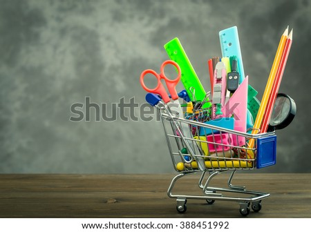 Shopping trolley with stationery items from right side of table on gray background with copy space - stock photo