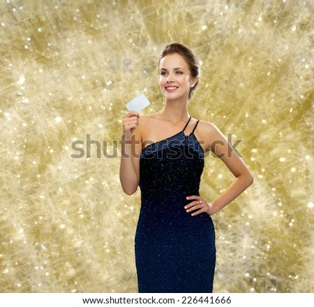 shopping, wealth, holidays and people concept - smiling woman in evening dress holding credit card over yellow lights background - stock photo