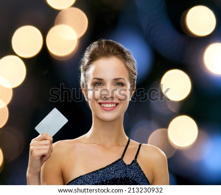 shopping, wealth, money, luxury and people concept - smiling woman in evening dress holding credit card over night lights background - stock photo