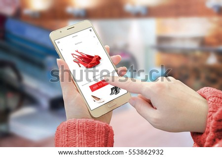 Shopping web site app on smart phone. Woman holding mobile device and buy red shoes. City shopping center in background.