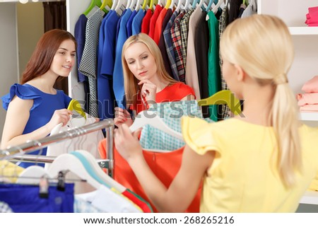 Shopping with friends. Selective focus on two female shoppers assessing choice of their friend standing in front of them with a hanger - stock photo