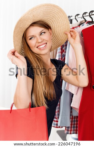 Shopping woman dreaming of travel and vacation. Young attractive Caucasian model with gift bags in retail clothes shop choosing hat.  - stock photo