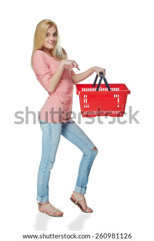 Shopping woman. Full length casual young woman standing smiling with empty shopping cart basket, over white background