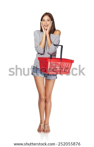 Shopping woman. Full length of surprised casual young woman standing with empty shopping cart basket holding her head in amazement and opened mouth, over white background - stock photo