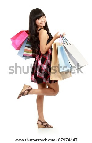 Shopping woman happy smiling holding shopping bags isolated on white background. Lovely fresh young Asian female model. - stock photo